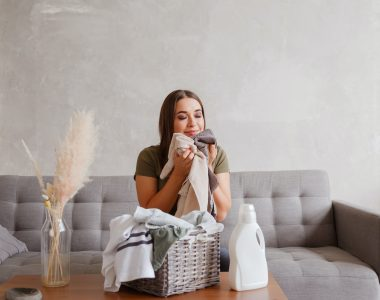 girl enjoys clean and smelling towels after washing with new detergent gel e1604115912382