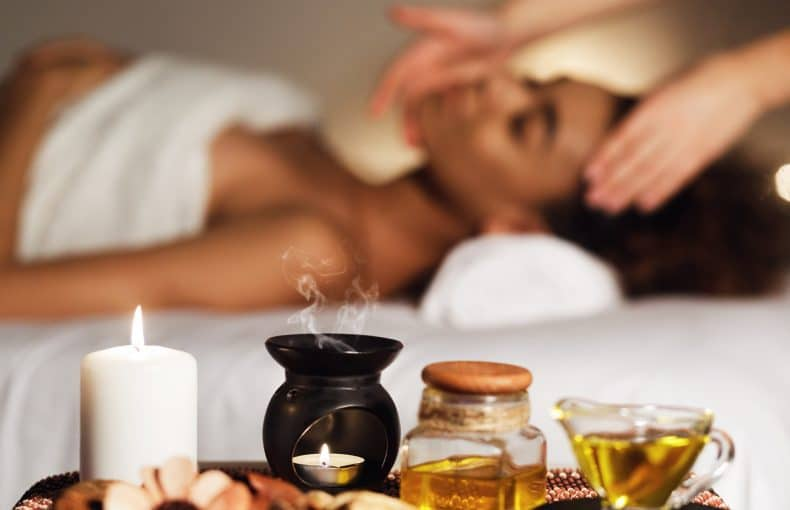 Aroma spa composition with candles and relaxing woman